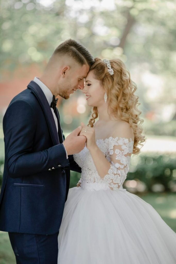 groom and bride with long curled hair extensions facing each other affectionately