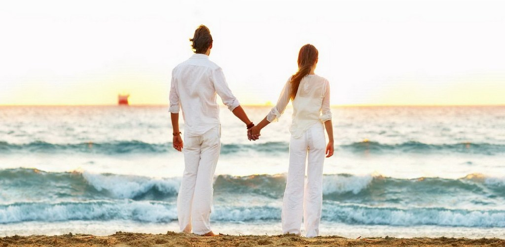 A young couple standing hand in hand on the beach