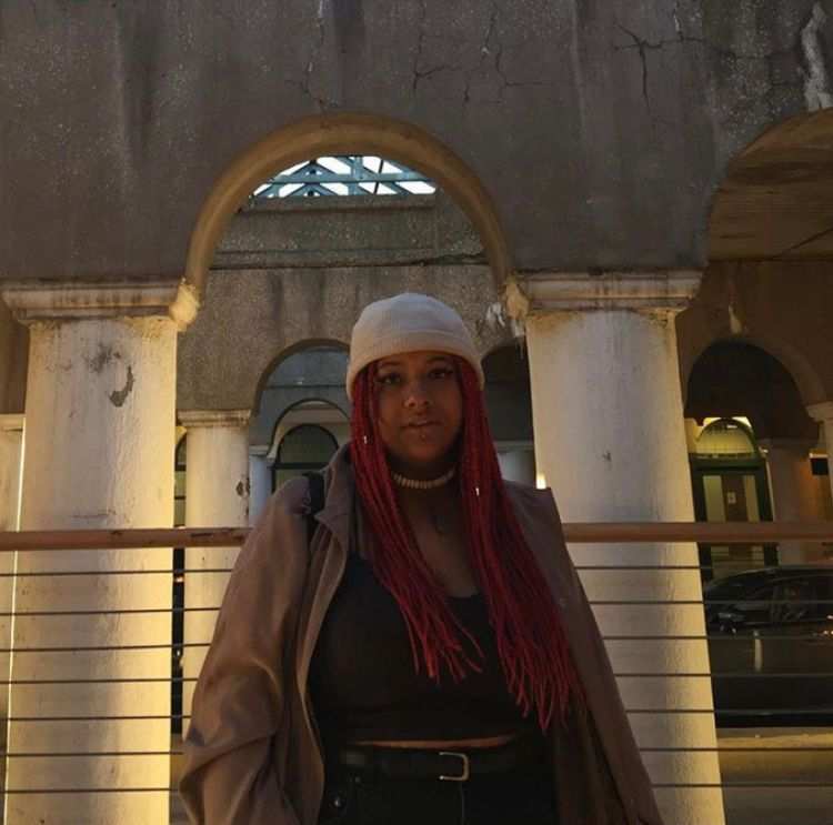 A brown-skinned Black person with long red braided hair is standing on the sidewalk under a street underpass structure. Their body is facing towards you and their eyes are looking straight ahead. They are wearing a white knit beanie and an oversized light brown trench coat that's opened up. You can see that under their coat they're wearing a cropped black tank top and black jeans with a black belt. The person is wearing a choker necklace with small white vertical beads on it. They are wearing winged black eyeliner. You also see that they are wearing a silver stud in their lip piercing under the center of their bottom lip.