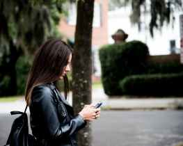 woman in black leather jacket holding smartphone