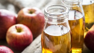 Glass bottles filled with vinegar and red apples near them