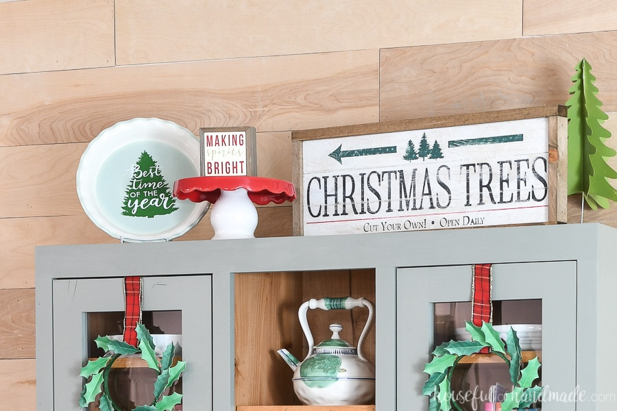 Top of a hitch decorated for Christmas with a Christmas tree farm wood sign, cake plate, Christmas pie plate and trees.