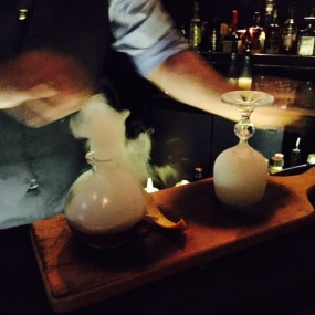 The smoked cocktail being created. The bartender actually set fire to the wooden board.