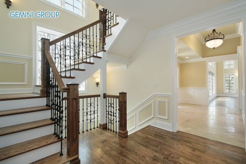 Foyer in new construction home with wood staircase