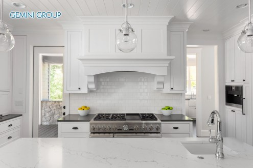 White Kitchen Interior Detail with Island, Range, Oven, Cabinets, and Hardwood Floors in New Luxury Home