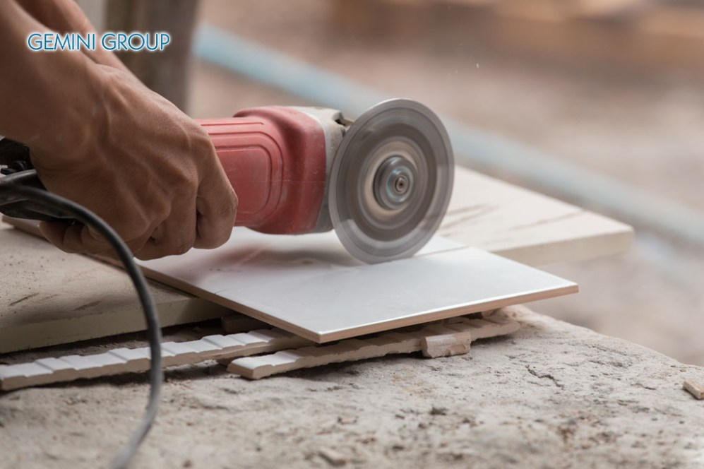 worker cutting a tile using an angle grinder at construction site