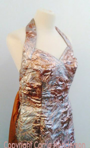 A colour photo showing the bodice of a silver and tan tight fitting halter neck gown displayed on a mannequin. The image is copyright Carrie Henderson.
