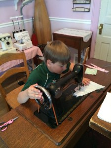 A present day colour photo of a blonde haired boy sitting in a sewing room stitching using a treadle sewing machine. His hand is on the wheel to turn it.
