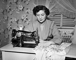 A black and white photo taken circa 1940s of a woman sitting behind a desk sewing with a sewing machine.