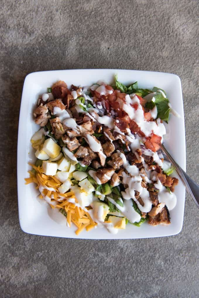 BBQ chicken cobb salad is the perfect summer dinner loaded with barbecued chicken, bacon, hard boiled egg, avocados, and more, on top of crispy romaine lettuce.