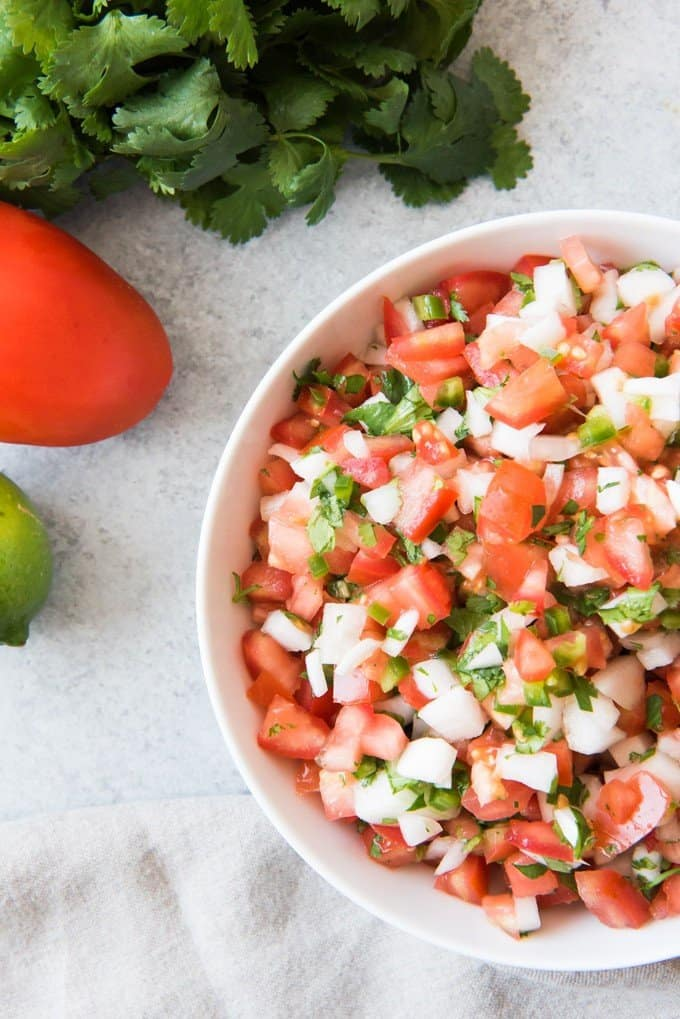 Even better, there is no cooking involved in making pico de gallo so it's especially good during the summer when it's too hot to cook much!  You just chop up the tomatoes, onions, jalapeno, garlic, and cilantro, toss it with a little lime juice and a bit of salt, and you're good to go!  And you can keep it mild or hot depending on how much jalapeno you add.