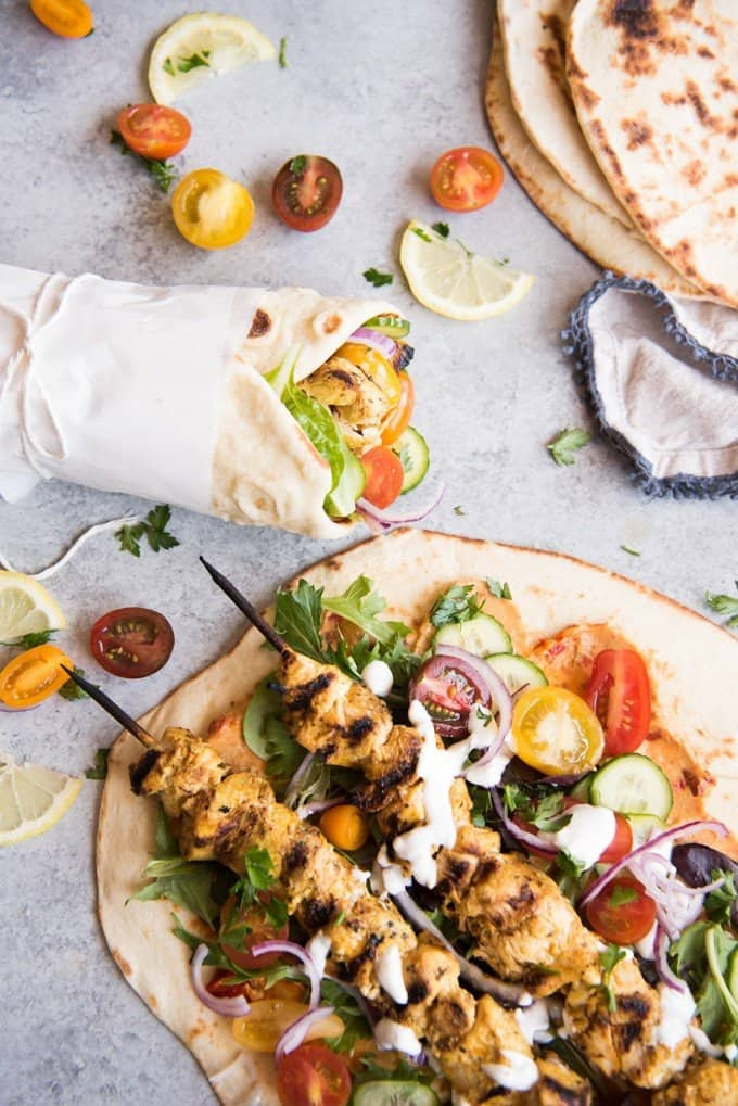 Grilled Chicken Shawarma Wraps are inspired by middle eastern street food where chicken is marinated in spices and then roasted on a spit to perfection and wrapped up in flatbread for a delicious sandwich.  Beats takeout or fast food any day! Perfect for salads as well!