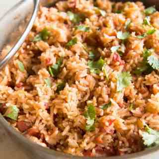 Homemade Mexican Rice (aka Spanish Rice) is a family favorite side dish that goes perfectly with any Mexican entree, from enchiladas to chimichangas! This homemade Mexican rice is easy to prepare and the flavor is as close to authentic Mexican rice as I think you might get without going to Mexico itself!