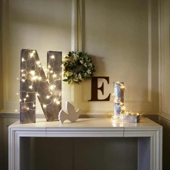Wooden letters spelling out Noel on console table decorated with fairy lights.