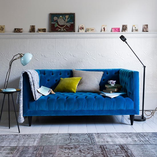modern living room with blue velvet sofa and task lighting living