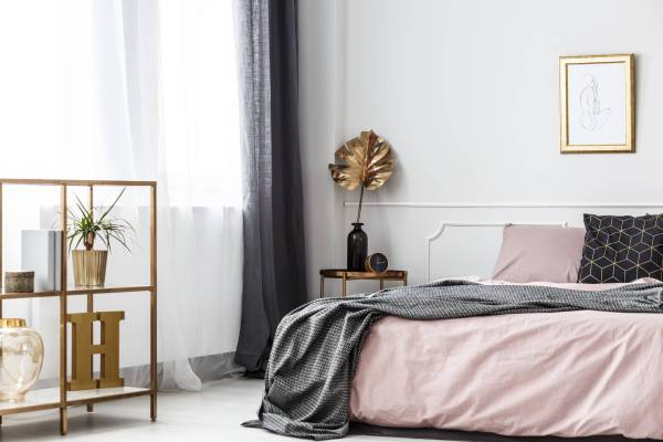Gold leaf on table next to bed with pink bedsheets against white wall with poster in bedroom interior