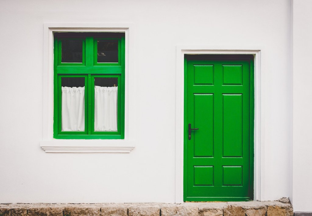 A white house with its doors and window frames painted green.