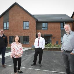 Four people outside a new housing development in Ordsall, Salford.