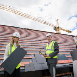Three people on a roof at a housing development in Wirral.