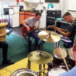 Four people playing musical instruments at supported accommodation in Kent
