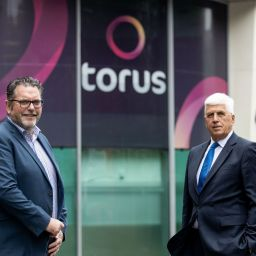 Torus Group's chief executive Steve Coffey and its chair Graham Burgess standing in front of Torus' logo.