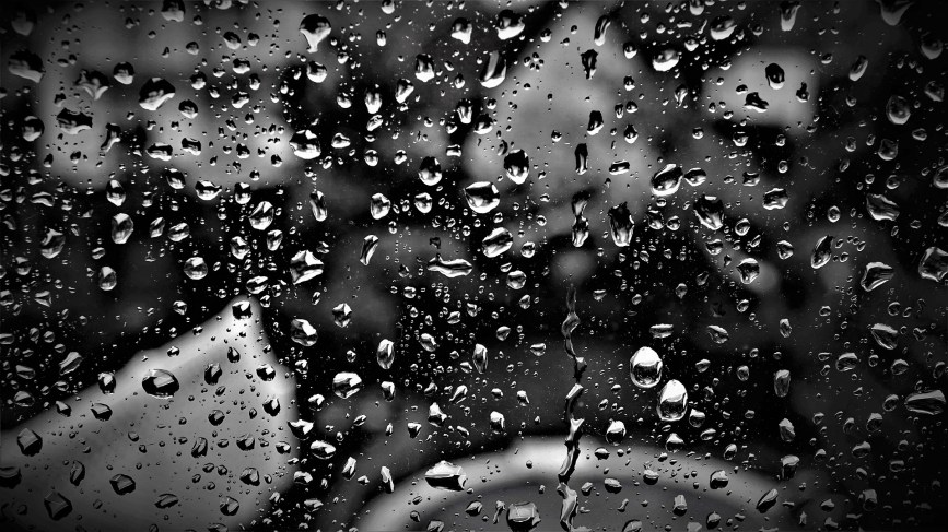 Rain dribbling down a window pane in front of a black and grey background.
