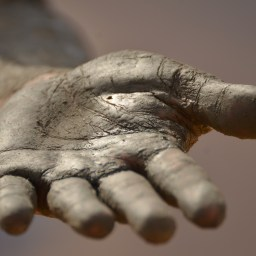 An outstretched hand made of clay.