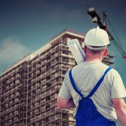 A builder standing with his back to the camera looking at a high-rise building under construction.