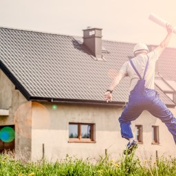 A man in blue overalls jumping for joy outside a newly built house. He is holding a blueprint.