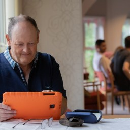 A South Tyneside Homes tenant sat at a table using a tablet.