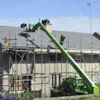 Contractors repairing the roof of a house.