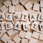 """A collection of wooden Scrabble tiles arranged to read """"Mental health""""."""