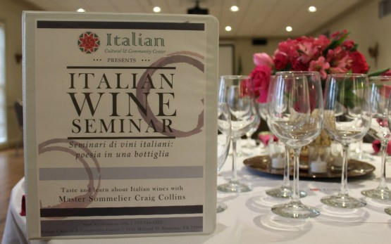 Photo of a sing announcing the Italian wine seminar and wine glasses on a table.