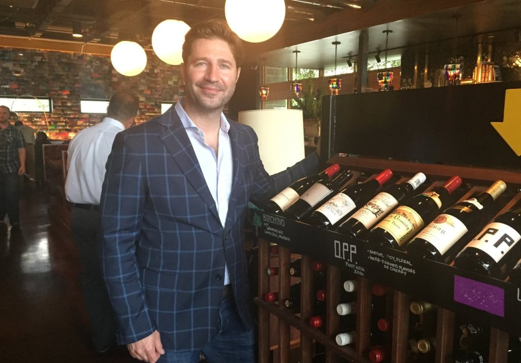 Photo of Brent Karlicek standing next to a rack of wine.