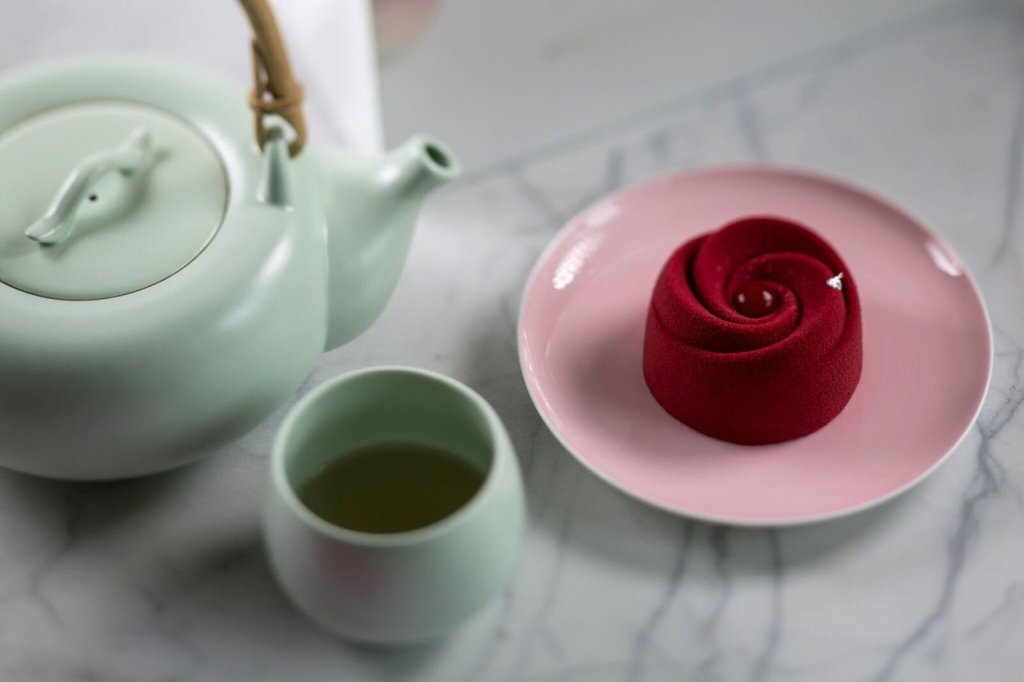 Picture of a tea pot and cup of tea, shot from above.