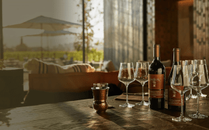 Wine glasses with wine bottle sitting on a table in a dark room with patio background