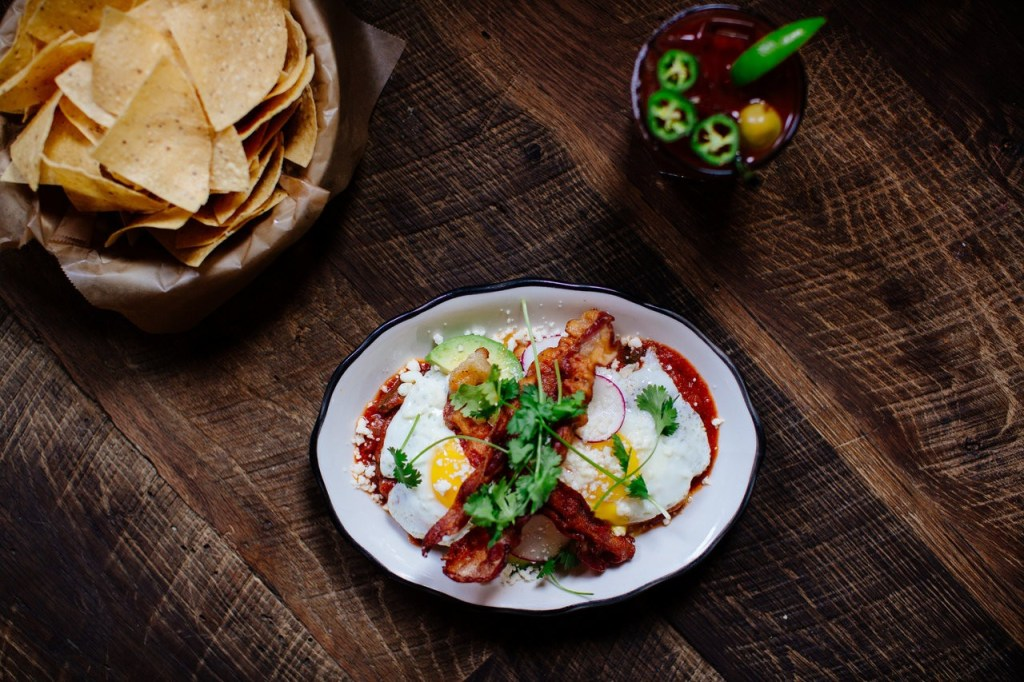 Image of a plate of huevos rancheros with tortilla chips and a drink with jalapeno in it
