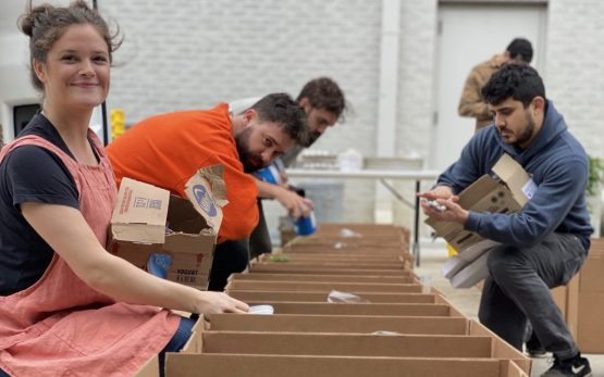 Employees of Goodnight Hospitality prepare boxes of food for fellow hospitality professionals