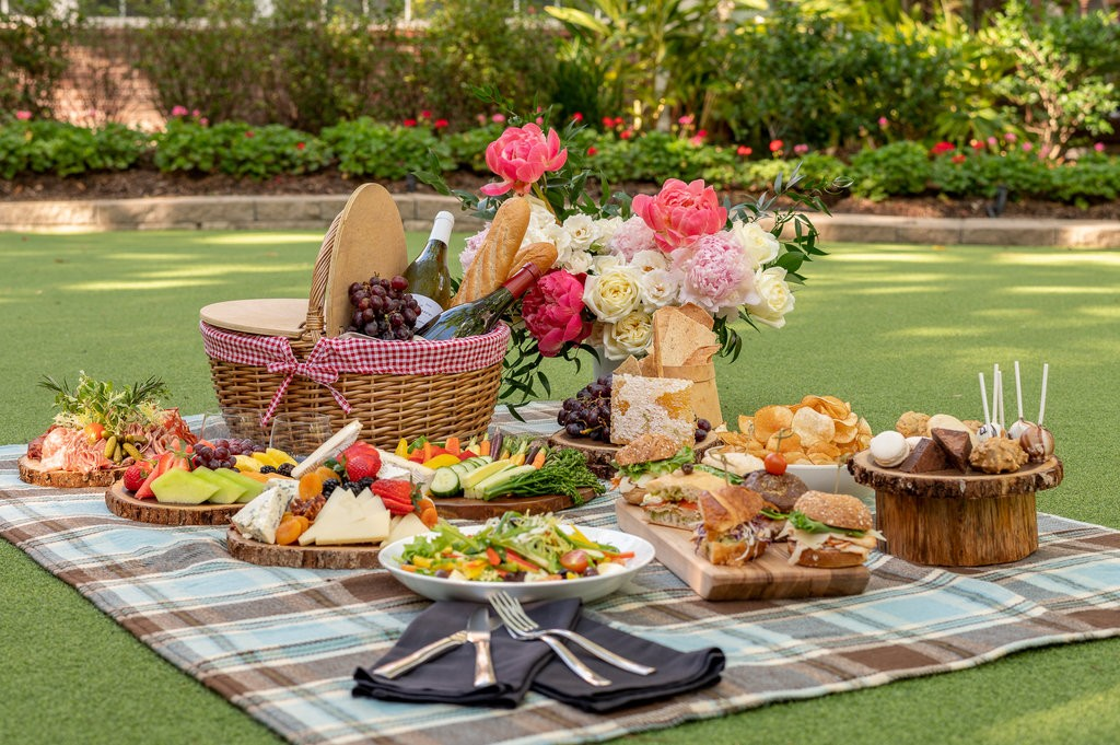 Photo of a picnic basket with baguettes and a bottle of wine, along with a blanket spread with desserts, salads and silverware