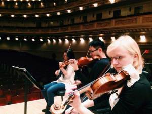 Musicians playing violins at Carnegie Hall.