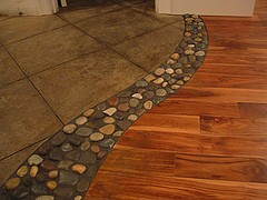 River rock between wood and tile floors. LOVE THIS!