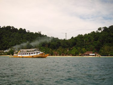 A ferry passes by a resort on Koh Ngai