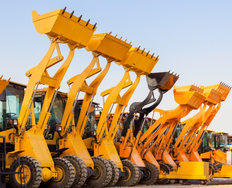 Row of heavy construction excavator machine against blue sky in a construction site.