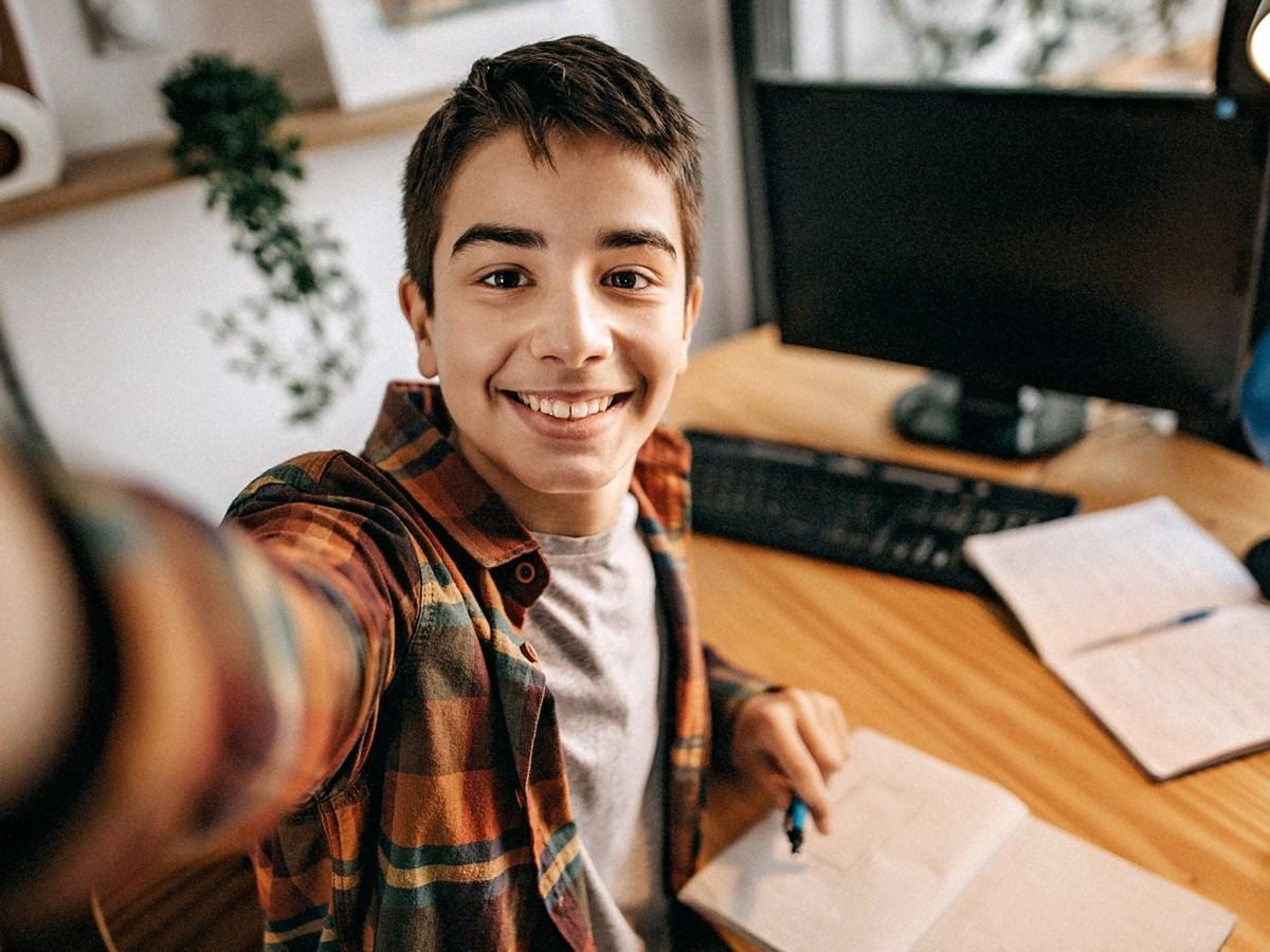 Teenage boy doing selfie while studying