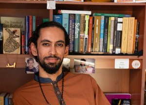 """""""Meet Asad Dandia"""" text graphic, portrait of Dandia in front of his library, looking at us."""