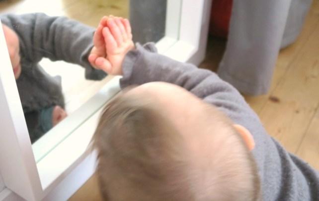 bébé joue avec le miroir