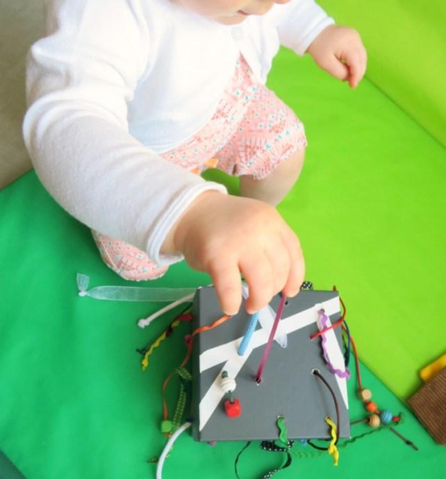 bébé joue avec rubans et fils à tirer DIY 12-18 mois