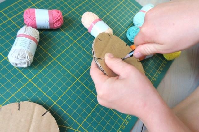 percer un rond en carton pour fabriquer des bracelets brésiliens