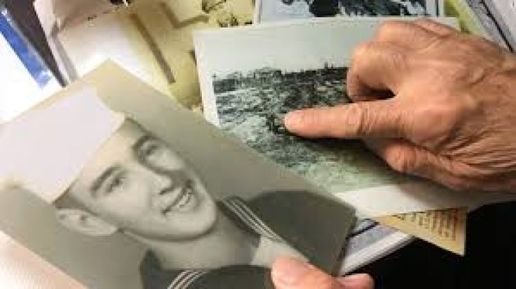 Shigeaki Mori pours over photos and documents collected on 12 POWs killed by bomb in Hiroshima.
