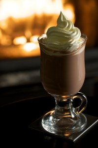 Creamy hot chocolate with whipped cream by the fireplace.